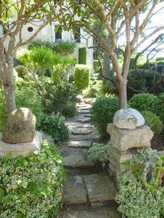 Columns of stacked stone with rounded stone toppers mark entrance to a pathway.  This as La Louve, Nicole de Vésian's garden,  Taken by Lynda Harris www.lyndaharris.com