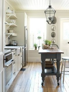 I think I love everything about this kitchen! old wood floors, open shelving, island a different colour (and a cool shape to it) farmhouse sink, cool lantern light fixture, etc etc!