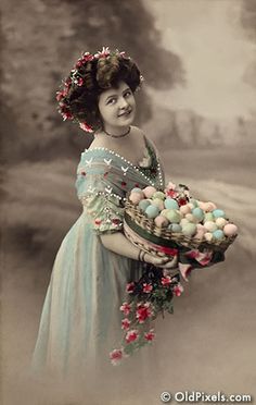 Woman with a basket of colored Easter eggs - A Victorian Era hand-tinted photograph, circa 1915.