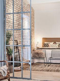 Chambre parentales (j'adore cette porte-verrière, ces fauteuils en métal en boud de lit, les fourures, le ling de lit, le mur en briques, etc♡)