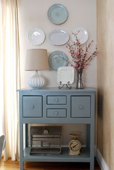 This beautifully painted cupboard in blue-grey fits in well with beige and white scheme accompanied by plates in matching hue which compliment the unit . . .