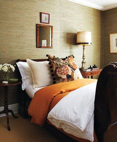 burnt orange accents on an earthy base { the textured wall paper makes the room so cosy }