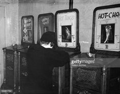 A boy looks through the viewer atop a peep show machine which plays the erotic International Mutoscope Reel Company production 'Hot Tango,' early 20th Century. Other titles for features seen on nearby machines, which describe themselves as 'Artistic Figure Studies,' include Rose of my Heart,' 'Vamping Venus,' and Hot-Cha!' This young fellow is looking into a 'Cail-O-Scope' which was a variation of the usual mutoscope technology and was invented in 1904 by the Caille brothers of France…