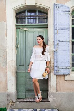 An off-the-shoulder white dress, gold sandals, a straw clutch and red lipstick: the perfect summer casual outfit