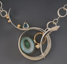 "limpet shell from the Pacific coast of Mexico set in 14ky gold and sterling silver with blue topaz.  1.25""h by 2""w."