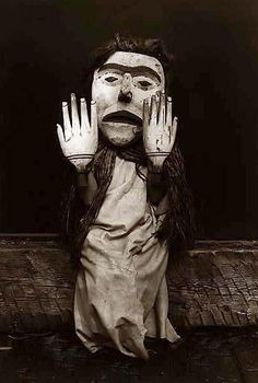 """Kwakiutl person wearing an oversize mask and hands representing a forest spirit, Nuhlimkilaka, (""""bringer of confusion"""")."""