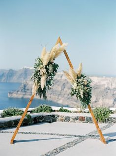 Wedding Flower Arrangements Triangle arch with pampas grass and king proteas- Modern wedding in Greece - Bohemian and Modern, Greek wedding in Santorini, Greece Grecian Wedding, Boho Wedding Flowers, Wedding Flower Arrangements, Wedding Centerpieces, Floral Wedding, Wedding Bouquet, Protea Wedding, Bohemian Wedding Decorations, Ceremony Decorations