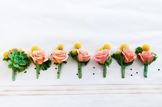 boutonnieres - photo by Artistrie Co http://ruffledblog.com/coral-wedding-with-a-flower-ceremony-backdrop