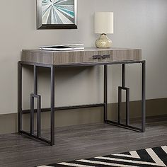 This sleek writing desk adds style and class to any room it's placed in. If you are looking for a modern desk to add to your home, this is an ideal piece.  Two easy-glide drawers. Finished on all sides for versatile placement. Diamond Ash finish.