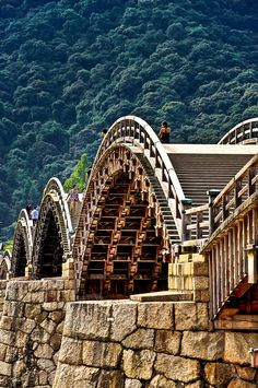 The Kintai bridge is located in Iwakuni, Japan. The bridge is 547 feet long. The bridge is over the Nishiki River, elevated 21 feet. The bridge is constructed of wood.