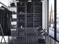 Ein Bekleidungsgeschäft mit VITTSJÖ Regalen und VITTSJÖ Satztischen in Schwarzbraun/Glas und METOD Korpussen Holzeffekt schwarz