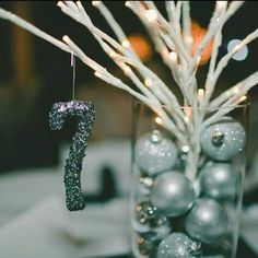 Styrofoam numbers covered in glitter and hung from a branch of a table centerpiece. I love arrangements that use ornaments and branches in glass vases.