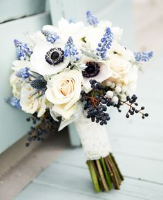 Wedding bouquet with blue anemones and strands of deep blue berries and sky-blue hyacinth