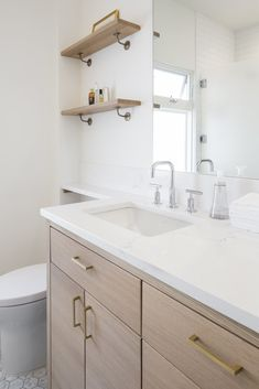 White oak cabinets and quartz countertops, again with brass pulls and brackets. Photo 7 of 12 in Craftsman Bungalow Gets a Scandinavian Kitchen & Bath by Model Remodel. Browse inspirational photos of modern bathrooms. Oak Bathroom, White Bathroom Cabinets, Bathroom Flooring, Bathroom Ideas, White Cabinets, Bathroom Storage, Bathroom Shelves, Small Bathroom, Master Bathroom