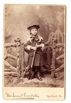 Cabinet photo, boy in skirt suit, with toy rifle