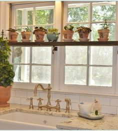 An aged pallet shelf with aged terracotta numbered flower pots warm up my white kitchen!