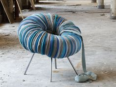 Furniture Ideas - 28 Accent Chairs For A Dramatic Living Room | Strips of fabric cover an inner tube that's been attached to the metal base to create a textured chair.