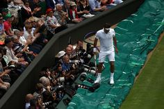 Roger Federer stands on the rain cover on Centre Court after chasing down a ball from Mikhail Youzhny. - Tommy Hindley/AELTC