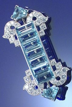 AQUAMARINE AND DIAMOND BROOCH, PROBABLY BY CARTIER, CIRCA 1925. Of geometric design, centring on a line of step-cut aquamarines between stylised scrolls of brilliant-cut diamonds and triangular-shaped aquamarine terminals, numbered, unsigned.
