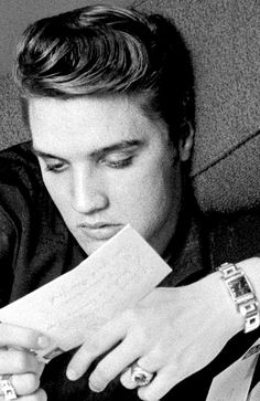 Elvis Presley photographed by Alfred Wertheimer while reading his fan mail inside his suite at the Warwick Hotel in New York ~ March 17, 1956