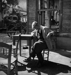 Man and cat dozing in a coffee-house at Pasabahçe. 1951. photo by Ara Guler