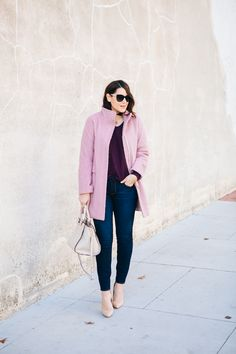 Winter outfit: pink coat, purple sweater, dark blue skinny jeans, nude accessories