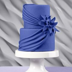 The cool blue color, richly textured swags and a lush gum paste lily make this cake a wedding sensation.