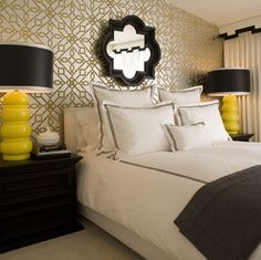 Metallic silver and gold geometric wallpaper, black quatrefoil mirror, black mirror, black shades, black wood nightstands, hotel bedding with black ribbon trim, charcoal gray flannel throw blanket, white and black cornice box, white drapes and white upholstered headboard.