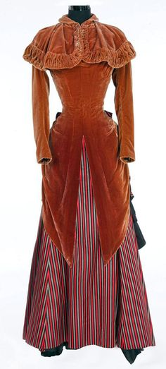 """Brown silk velvet period dress with red, grey, and black striped skirt and matching caplet. Worn by Kathryn Grayson as Magnolia Hawks when she and Howard Keel arrive in Chicago in """"Showboat"""" (1951)."""