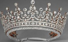 The 'Girls of Great Britain and Ireland'     Tiara was given to the future Queen Mary as a wedding present in 1893. The diamond tiara was purchased from Garrard, the London jeweller, by a committee organised by Lady Eve Greville.    a diamond festoon-and-scroll design surmounted by nine large oriental pearls on diamond spikes and set on a bandeau base of alternate round and lozenge collets between two plain bands of diamonds