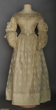 """2-piece fine wool w/ silk scattered floral brocade, fan F bodice, sleeve tops banded down w/ small pleats, blonde silk lace trim, glazed cotton bodice lining, B 30"""", W 22"""", Skirt L 36"""", (tiny spots, many moth holes) fair; t/w 1 c. 1830 white cottonpetticoat, hand quilted in diamond pattern w/ flower & vine hem band quilted (waist band missing, scattered tiny brown spots) very good."""