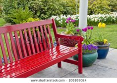 Red garden  bench on patio surrounded by pots of colorful spring flowers by TDMuldoon, via Shutterstock
