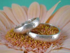 Zwei Ringe aus 925er Silber, deren Oberfläche gewölbt und fein mattiert ist. Sie zeigt das typische Hammerschlag-Muster, welches beim Schmieden ent...