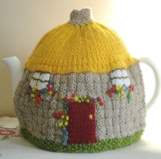 Hand knitted Tea Cosy designed to look like an old English Country Cottage with a traditional thatched roof Has a red door one side and a blue door on the other, with a profusion of flowers round the doors and under the windows. This cosy is double-thickness to keep your tea hot Designed and made in my smoke-free Garden Studio in England Measurements: Approx 19 inches (49cm) all round base 7.5 inches (19cm) high, excluding chimney Photographed on a 2-pint tea pot Made with...