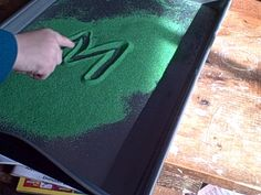Writing letters in colored sand
