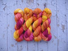Hand dyed sock yarn. This yarn has been dyed in a bright golden yellow, orange, a pinkish red, and a bright purple fuchsia along with some mixing of these colors and some lighter/white areas. There is also a few speckles of a deep red mixed throughout. This listing is for 1 skein of Staple Sock.  This yarn is a repeatable colorway but due to the nature of hand dyed yarn may vary slightly from what is pictured. Looking for more than what is listed? Send me a convo!  Colorway - Plumeria…