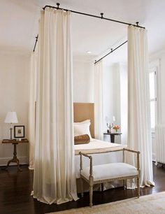 Pinch-pleated drapery panels suspended from an iron rod in the ceiling create a lovely ethereal effect in the bedroom.