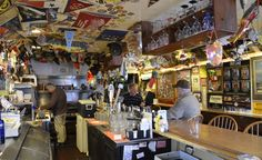 Smallest Bars in the World: Sports pennants, vintage postcards, yacht-club flags, and maps of Lake Erie wallpaper the ceiling and walls of Close Quarters Pub, in Avon Lake, Ohio. (Courtesy Visit Lorain County/Flickr)
