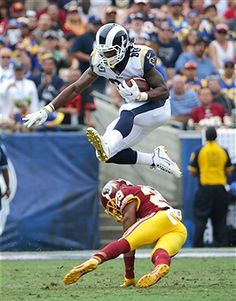 Todd Gurley  30 of the Los Angeles Rams leaps over Kendall Fuller  29 of 1ecf7f86a
