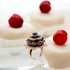 Bulgari Festa collection Chocolate Cake ring with onyx, coral, emerald, sapphire and diamond details. Set in 18-carat rose gold. Photographed in front of cherry cupcakes with white icing. http://www.thejewelleryeditor.com/jewellery/article/bulgari-festa-high-jewellery-collection-jewels-watches/ #jewelry
