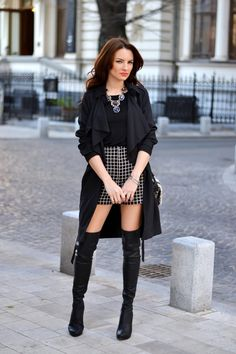 Black trench, boat neck top, black and gold grid print high-waisted shorts and knee high boots