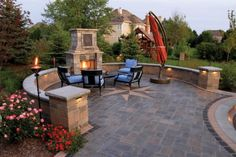 Patio with fireplace and surrounding walls by Unilock with Richcliff paver