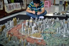 Artist Stacks 50,000 Coins with Chopsticks to Create Glueless Replica of Chingqing, China