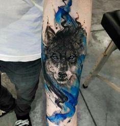 tatuajes de lobos, hombre con tatuaje en el antebrazo, tatuaje en azul y negro estilo acuarela, cabeza de lobo con ojos azules