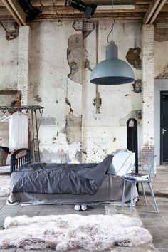 Een groot grijsbruin onderlaken, een stonewashed blauwe dekbedhoed en fris gestreepte kussens maken samen een prachtig plaatje.