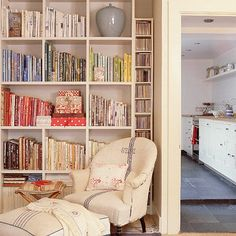 Living room bookshelves. Keep clutter to a minimum by adding adequate shelving space for music and books. The armchair and footstool are both covered in vintage French linen from Elizabeth Baer, adding interest and pattern.