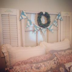 Repurposed window and shutters as a headboard + hand-painted burlap banner + wreath