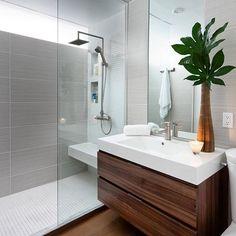 Para quebrar o branco desse banheiro, a área da bancada tem piso em porcelanato imitando madeira e o armário sob a bancada foi revestida com MDF no mesmo padrão. Na área de banho dois tipos de acabamento fizeram um mix muito bonito. Adorei!!!!!!