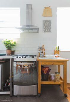 Cozinha integrada de apê compacto tem piso de cimento queimado, revestimento de subway tiles e móveis soltos como o carrinho de madeira.