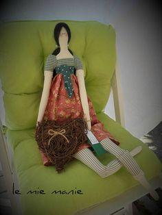 Bambola tilda, realizzato interamente a mano, in stoffa di cotone e imbottitura al 100% polyestere. Il modello disponibile ha la gonna salmone, la maglia e le panta nella tonalità del verde e tiene tra le mani un bel cuore di vimini. Le bambola è alta 62-63 cm. Non è un giocattolo, ma